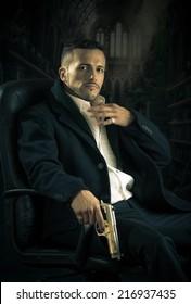 Elegant handsome latin man gangster mafia spy hitman assassin sitting in a chair holding a gun over dark background