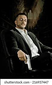 Elegant handsome latin man gangster mafia spy hitman assassin with closed eyes sitting in a chair holding a gun over dark background