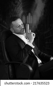 Elegant handsome latin man gangster mafia spy hitman assassin sitting in a chair pointing gun up black and white portrait