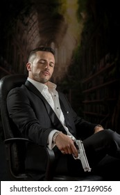 Elegant handsome latin man spy hitman assassin looking down sitting in a chair holding a gun over dark background