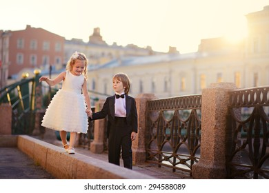 An elegant handsome little boy in a tail-coat and his pretty little girlfriend walking along a beautiful old bridge at sunset on a sunny warm summer evening. Kids in the city. Saint-Petersburg. Russia