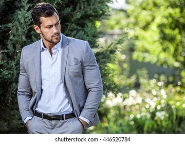 Elegant handsome man in classical jacket poses outdoor.