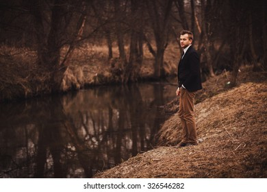 Elegant handsome man in suit poses in forest near river. Copy space