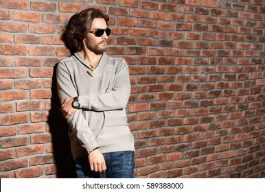 Elegant handsome young man wearing pullover and jeans standing by the brick wall. Men's beauty, fashion. Men's barbershop, Hairstyle.