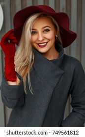 Elegant happy beautiful young woman in stylish hat and fashionable gray coat posing near wooden wall