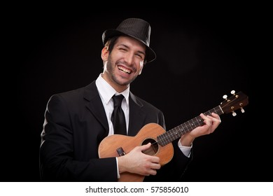 elegant happy man singer musician playing ukulele guitar isolated on black