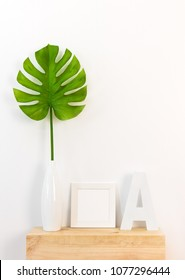 Elegant home decor with white picture frame, green tropical leaf in a vase, and letter A on wooden surface.