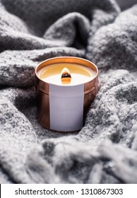 Elegant home decoration with wooden wick burning candle and knitted blanket