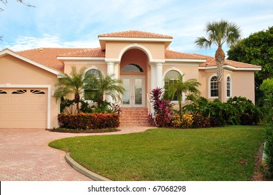 Elegant home, with huge archway covering double door entrance,  flanking columns, lush tropical landscaping and wide brick driveway joining the sidewalk  completes this modern design.