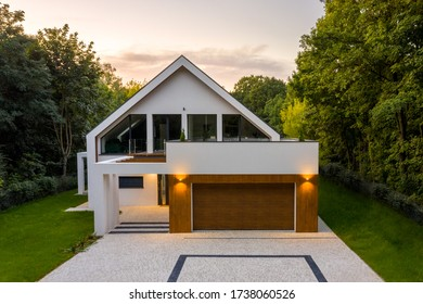 Elegant house with balcony, garage, cobblestone driveway, green lawn and lights on, exterior view during sunset