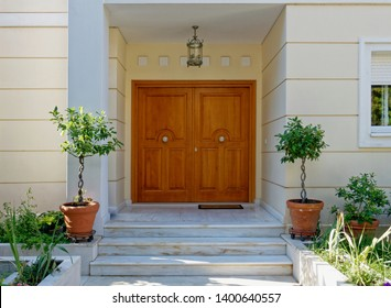 elegant house entrance portico with natural wood double doors and potted plants