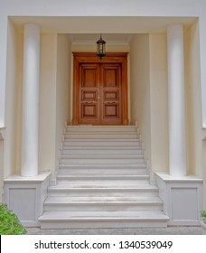 elegant house portico with columns and stairs to natural wooden door
