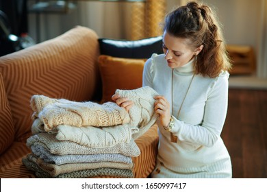 elegant housewife in white sweater and skirt at modern home in sunny winter day sitting near couch checking sweaters for moth larvae or other damage.