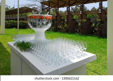 Elegant ice sculpture drinks holder with frozen red roses and four cooling champagne bottles inside ready to serve.