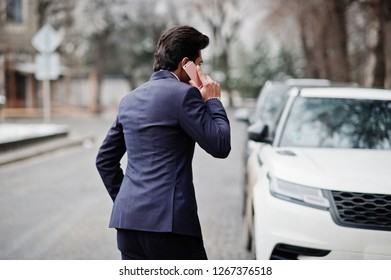 Elegant indian macho man model on suit and pink tie posed against white business car and speaking on phone.