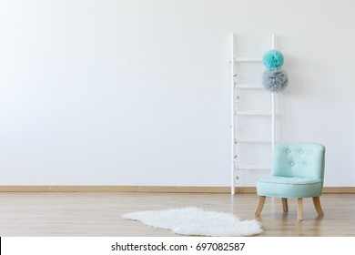 Elegant interior of children's room with a decorated ladder, a mint comfortable chic chair, and a fake animal skin lying on the wooden floor