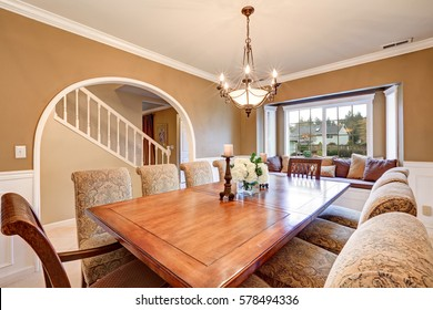 Elegant interior design of formal dining room with tan walls, wainscoting, arched doorway, window seat and large dining table with upholstered chairs. Northwest, USA