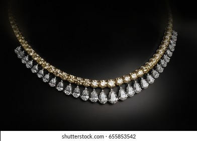 An elegant jewelry. Gold and diamonds necklace on black background.