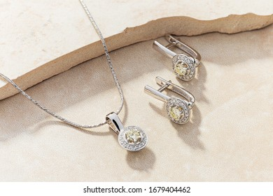 Elegant jewelry set of white gold necklace and earrings with diamonds. Silver jewellery set with gemstones. Product still life concept