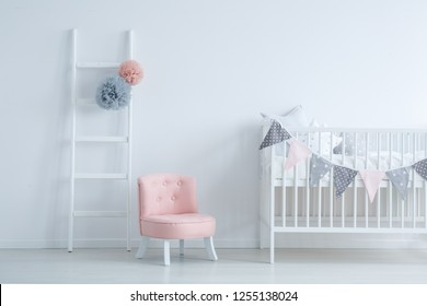 Elegant kid's room with white wooden ladder with grey and pastel pink pompons, small cute armchair and crib with star shape pillows, copy space on empty white wall