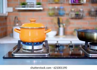 Estúdio de cozinha elegante para o negócio de alimentos cozinhar no hotel tem um equipamento de luxo e closeup panela amarelo no fogão a gás que tem fogo.