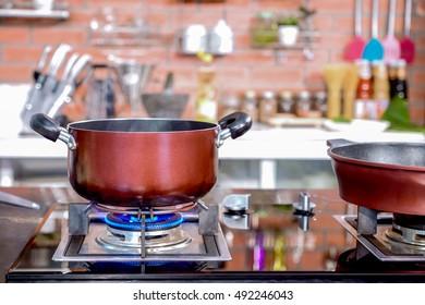 Cozinha elegante para cozinhar oficina no hotel tem um equipamento de luxo e closeup pote no fogão a gás que tem fogo.