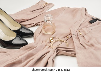 Elegant ladies fashion ensemble with a stylish dress, classic patent leather black court shoes, gold bangles and bottle of perfume or scent laid out ready to wear on a white background, low angle
