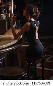 elegant lady in black dress, in restaurant at a bar