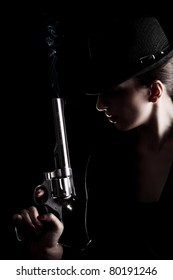 elegant lady in black holding a revolver