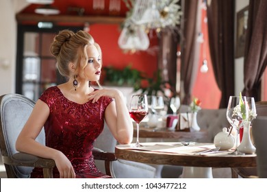 Elegant lady clothed in long red dress with glass of red wine in restaurant. Luxury woman, dating, royal life concept.