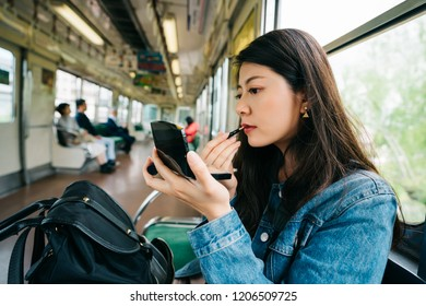 elegant lady doing makeup on the subway, she is using a red lipstick. beautiful girl going to work by train. Japanese office lady makeup concept.