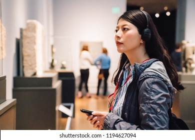 an elegant lady in the exhibition, wearing earphone to hear the voice guide
