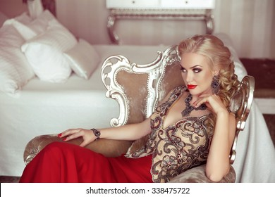 Elegant lady. Fashion beautiful sensual blond woman with makeup in luxurious prom dress with bijou, posing on modern armchair with sliver frames.