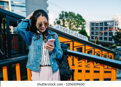 elegant lady flicks hair, using cellphone and waiting for the next angels flight railcar. Asian woman commute transport concept. young girl using online communicate app on phone.