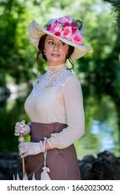 Elegant lady, from high society of the twentieth century, walking through a public park