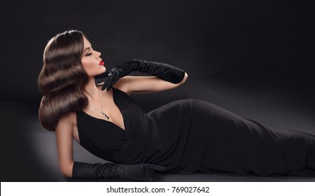 Elegant lady in long sexy dress with retro wavy hairstyle lying isolated on studio black background. Beautiful brunette woman in glamour gloves. Fashion style photo.