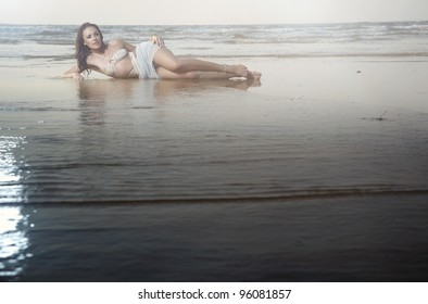 Elegant lady with perfect body lying at the beach. Natural colors and light