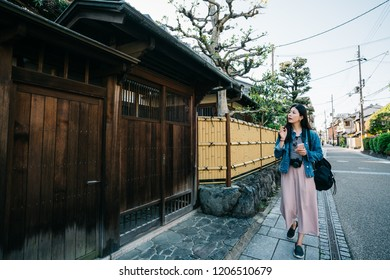 elegant lady pointing at Japanese traditional building which made by wood and she is looking for hotel. female traveler using booking app to find the hostel in Japan. Traveling tour in Asia concept.