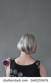 Elegant lady with silver hair holding a dark red dahlia, on gray background with copy space.