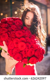 Elegant lady stands and keeps big bouquet of red roses in hands, on the street