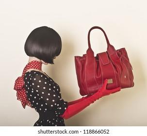 Elegant lady with stylish short hairstyle holding a bag