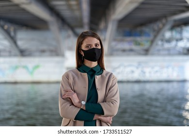 Elegant lady under a bridge wears a black medical mask to protect herself from coronavirus COVID-19, city portrait in Russia.