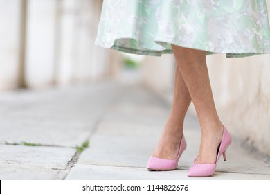 Elegant lady wearing stylish pink court shoes with stiletto heels crossing her legs as she stands on an urban sidewalk in a low angle view of her shapely legs
