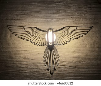 Elegant lamp looking like fenix bird hanging on white wall.