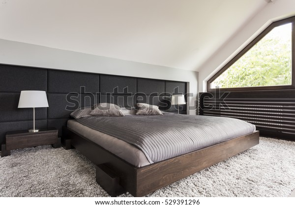 Elegant large bed in a dark frame in an attic bedroom