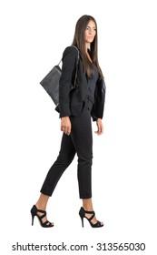Elegant Latin business female in black suit and handbag walking side view.  Full body length portrait isolated over white studio background.