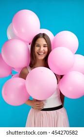 Elegant laughing girl with air balloons around her.Studio shot