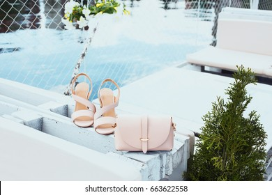 Elegant leather women's beige sandals on high heels and a stylish women's beige handbag on white wood pallet, near creative pool.  Fashion shoes image.