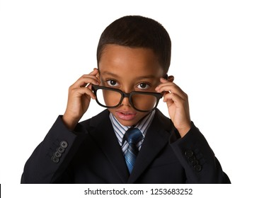 Elegant little african-american boy with glasses in business suit. Concept of leadership and success. Studio shot. Young boy posing.