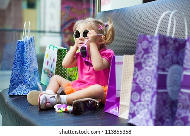 Elegant little girl posing on a big sofa in the mall on the background shop windows.